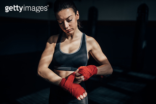 Female boxer wrapping bandages on hands