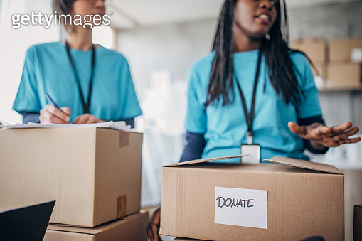 Diverse volunteers packing donation boxes in charity food bank