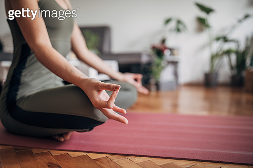 Young woman meditating on the floor in living room