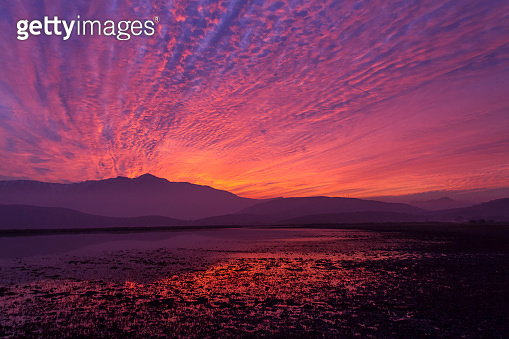 Beautiful Patagonia landscape of Andes mountain range with high mountains with illuminated peaks, stones in mountain lake, reflection, orange violet red sky at the sunset