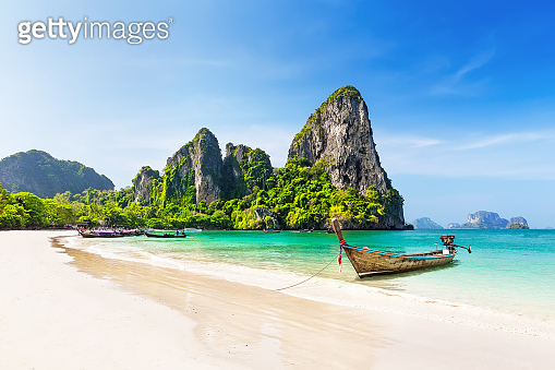 Thai traditional wooden longtail boat and beautiful sand beach.