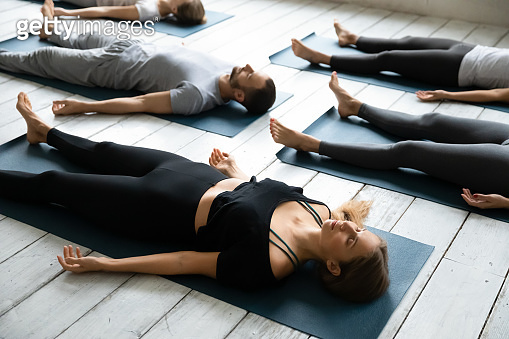 People resting after yoga workout lying in Shavasana Pose