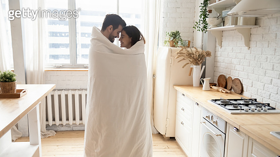 Young affectionate couple standing in kitchen wrapped with blanket