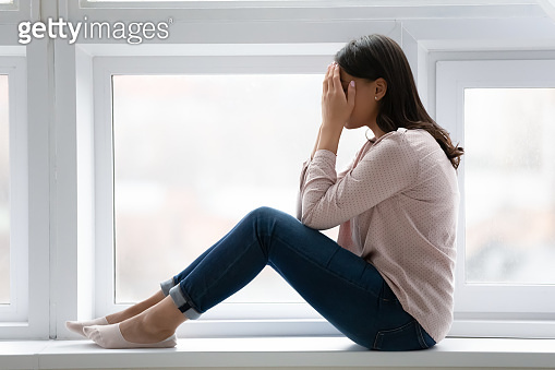 Depressed woman sitting on windowsill crying covered face with palms