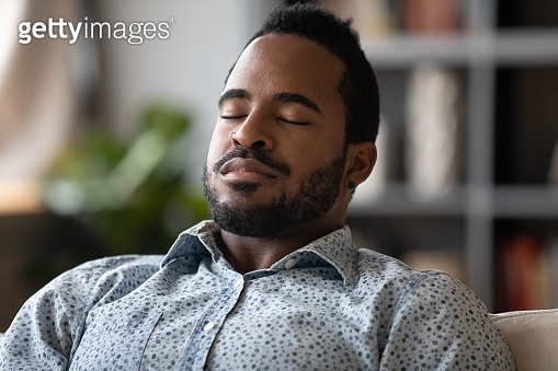 Close up African young man sit on couch closed eyes resting reduces fatigue