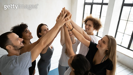 Happy multiethnic people in sportswear stacked hands together showing unity