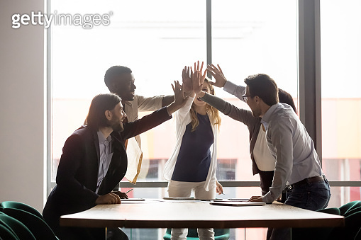Multiethnic business people giving high five celebrating common success