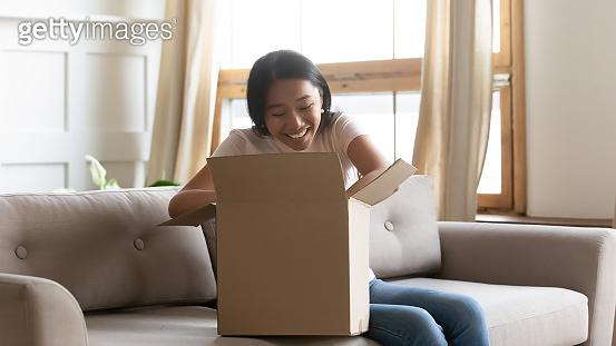 Curious asian female client unboxing online order.