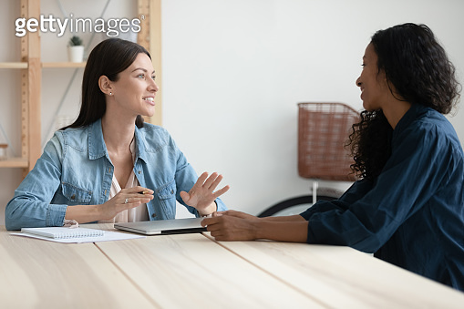 Diverse female colleagues talk at office meeting