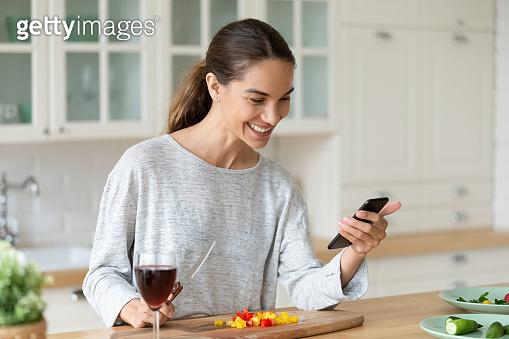 Happy lady holding phone preparing vegetable meal search vegan recipe