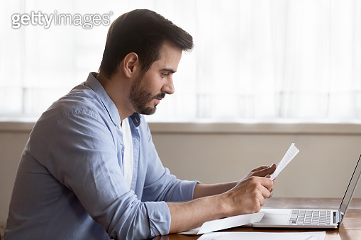 Focused millennial man read letter at home