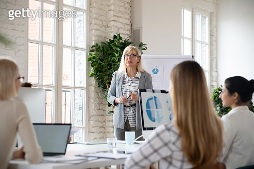 Middle aged skilled female team leader presenting company growth strategy.