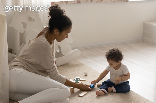 African American mother and cute toddler daughter playing wooden blocks
