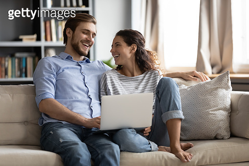 Happy couple relax on sofa using laptop together