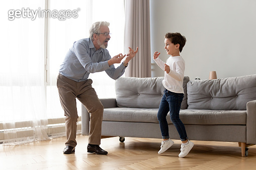 Full-length grandfather dancing with little grandson at home