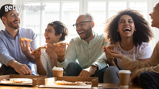 Laughing multi racial friends eating pizza indoors