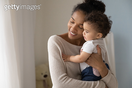 Loving biracial mom hug little baby toddler