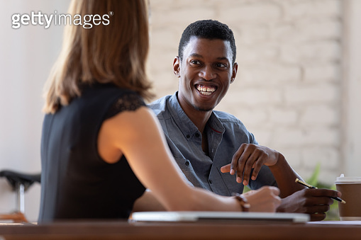 Multi-ethnic smiling teammates working together sitting at desk