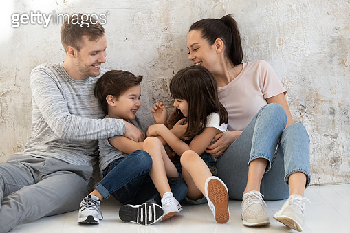 Happy young parents with little kids sitting on floor.