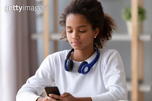 African teen girl with headphone search music in mobile app