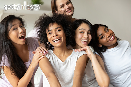 Happy millennial girls smile for picture at hen party