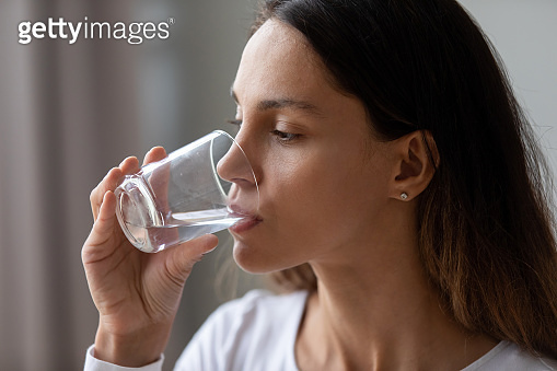 Caucasian girl hold glass drinking still mineral water
