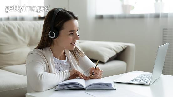 Smiling girl in headphones watch webinar on laptop