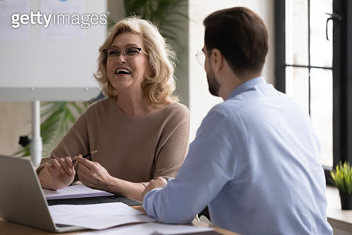 Happy mature mentor laughing at funny joke with partner indoors.