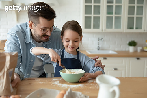 Caring young father helping small daughter preparing food.