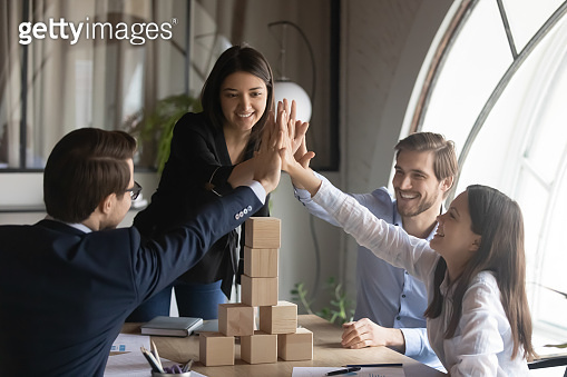 Excited diverse employees give high five at team meeting