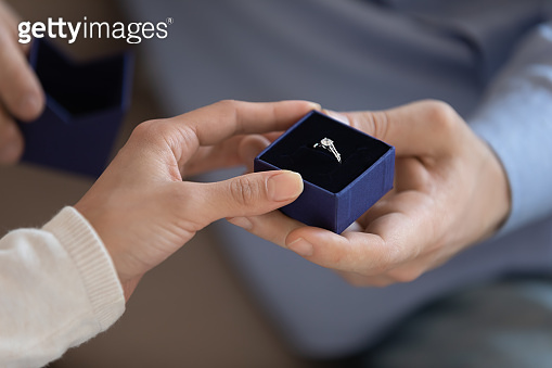 Young male presenting engagement ring to beloved female