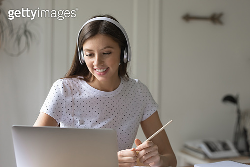 Smiling female student study on laptop at home