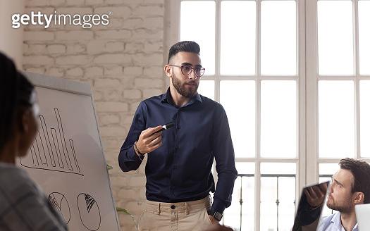 Arabic male coach talk making whiteboard presentation at briefing