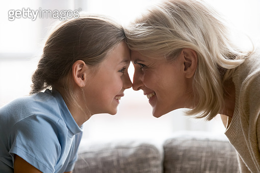 Happy school granddaughter and mature older grandmother touching foreheads.