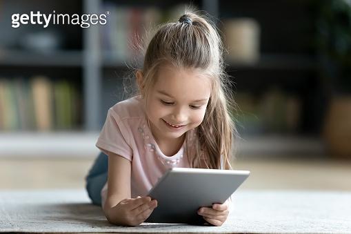 Little girl lying on floor in living room with tablet