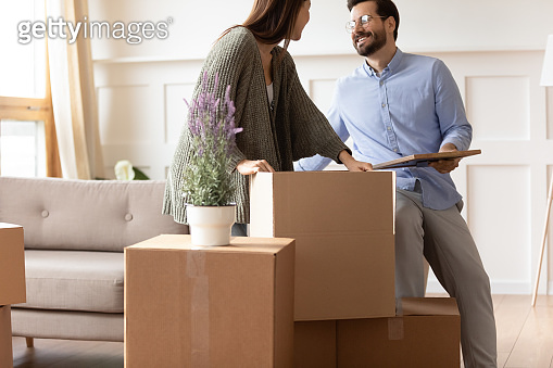 Excited young couple unpacking cardboard boxes, moving day