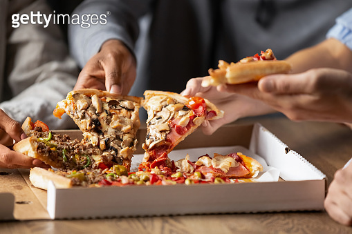 Close up of multiethnic friends share delicious pizza