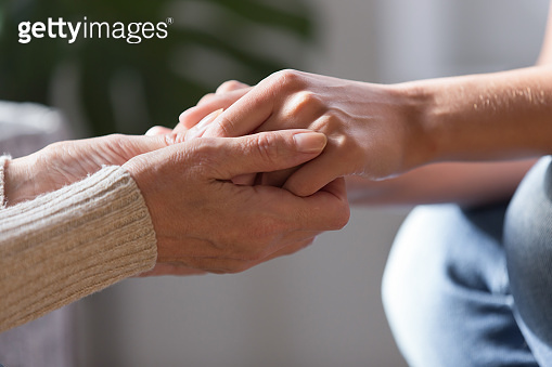 Two females holding hands close up view image