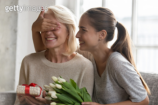 Cheerful adult daughter closed eyes mother before giving a gift