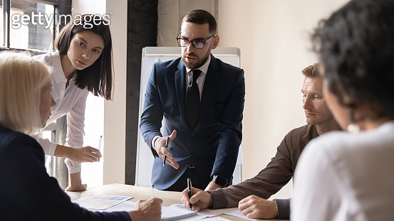 Confident businessman discussing project strategy with mature team leader