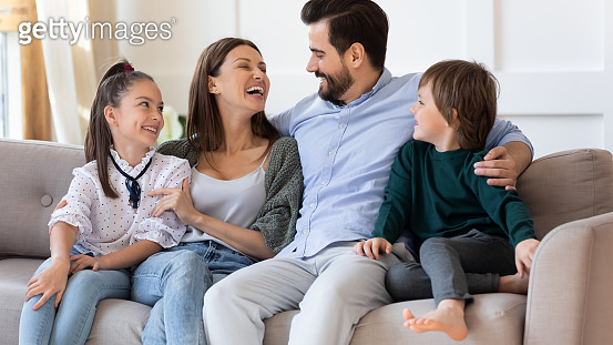 Happy mother and father hugging with children, sitting on couch