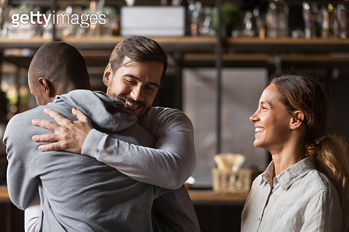 Overjoyed diverse friends embrace welcoming pal in bar