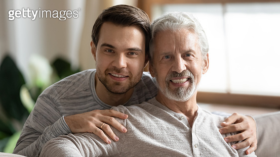 Portrait of loving senior dad and adult son hugging