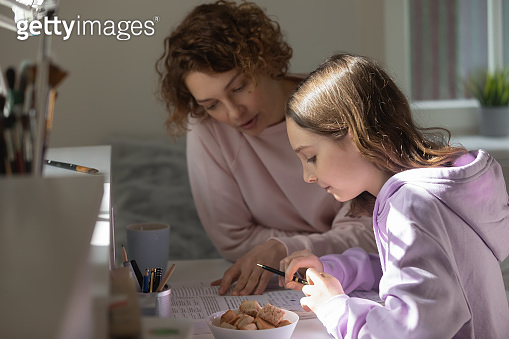 Caring mother helping to teenage daughter with school homework