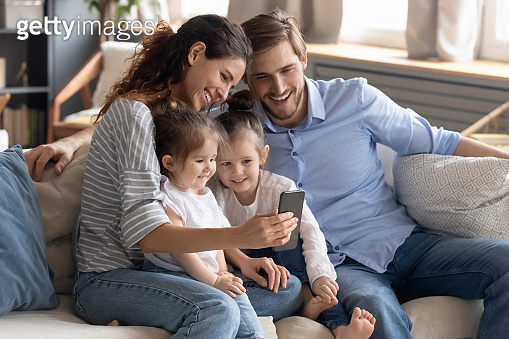 Smiling young mother and father with two daughters using smartphone