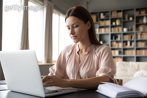 Focused woman working on laptop, sitting at desk at home
