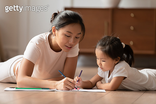 Vietnamese ethnicity woman drawing pictures with little kid.