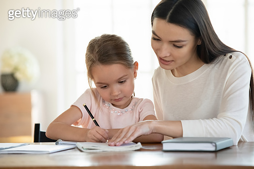 Affectionate young mother teaching small daughter reading writing.