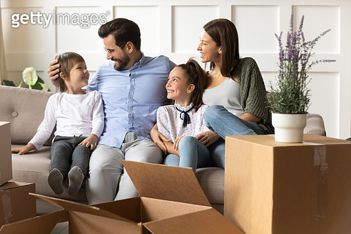 Happy parents with children relaxing on sofa on moving day