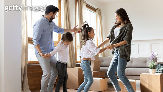 Excited parents with children celebrating moving day in new house